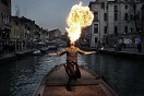 "A participant of a boat parade spits fire as boats with people wearing costumes sail on the ""Rio Canareggio"" during Carnival Carnival originates as a passage from winter to spring and traditionally during that time the license was granted to Venetian people to contravene the strict social rules imposed by the Serenissima Republic such as to lapse into games and parties. Hiding their faces behind masks gave the illusion that it was possible to change identity, sex and social class through an ambiguous exchange of roles. During the eighteenth century the Carnival made it's peak, however because of the fall of the Republic and the Austrian domination it was abolished and only recently made a cultural come-back that attracts hundreds of thousands of people that desire to live the nineteenth century atmosphere once again."